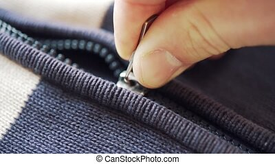 A hand zips and unzips a cardigan or a wool sweater. Very...