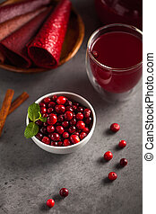 a handful of cranberries in a bowl and fruit drink in a glass on a gray background