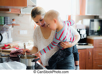 A handicapped down syndrome boy cooking soup with his mother indoors.