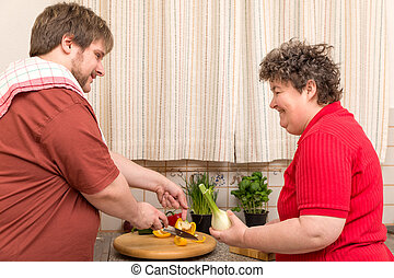 a handicapped woman and a young man in the kitchen