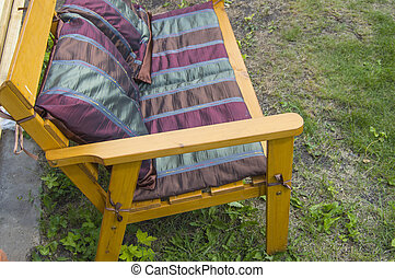 A handmade wooden chair covered with a textile blanket and Burgundy pillows stands on the grass in the garden on a Sunny summer day