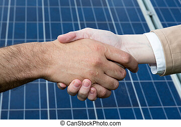 A handshake in front of solar energy panels