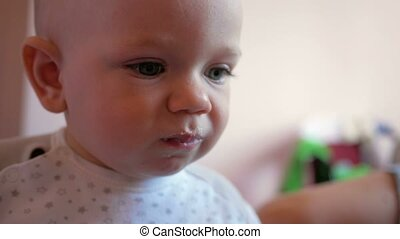 A handsome baby stares at one point and eating baby food with spoon. Tiny one year. Close-up