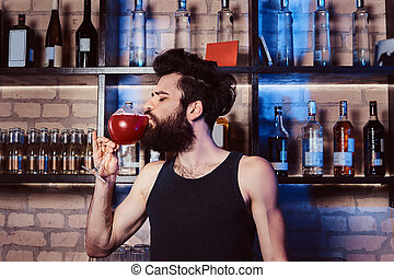 A handsome bearded bartender drinks a glass with Aperol spritz cocktail behind bar counter