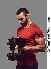 A handsome bearded male wearing sportswear doing exercise on...