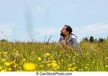 handsome bearded man sitting in a wildflower meadow