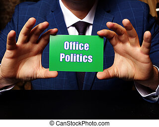 A handsome businessman showing a blank piece of paper with sign Office Politics . Close-up shot. Soft focus.