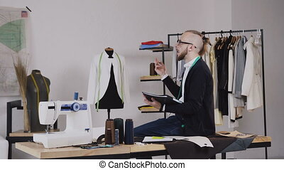 A handsome fashion designer sits on the table in the studio and draws sketches for tailoring the new collection of clothes. A young bearded tailor wearing glasses, dressed in a white shirt and a black blouse with a measuring handle on his neck, working in the atelier