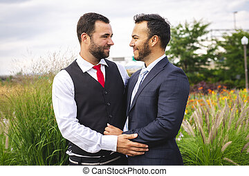 A Handsome gay male couple in the park on their wedding day...