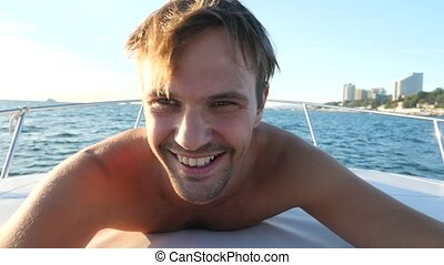 A handsome guy does selfie on board a yacht. 4k, close-up,...