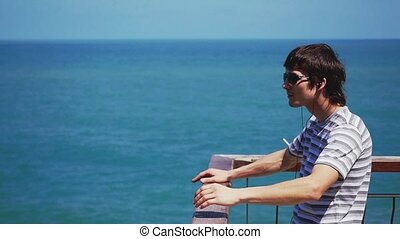 A handsome happy man with headphones and sunglasses listen to music on cellphone standing by the sea in slow motion.