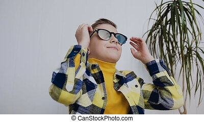 A handsome little boy with blue eyes wears sunglasses and looks aside. In the room, on a white background