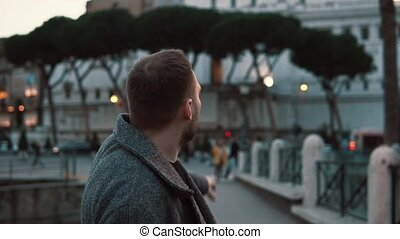 A handsome tourist man considering the roman sights in the centre of Rome in Italy in the evening and pointing.