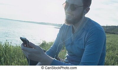 A handsome young man in glasses near the sea at sunset writes sms on a smartphone. A happy stylish man with headphones rewrites through the phone.