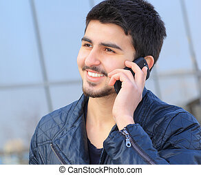 A handsome young man in plain clothes, talking the phone.