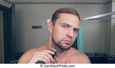 a handsome young man shaves his beard with an electric shaver, standing in the bathroom in front of the mirror. 4k, slow motion