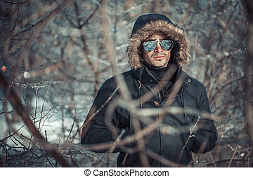 a handsome young man with spectacles in the Park in winter