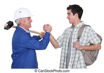 A handyman handshaking his trainee.