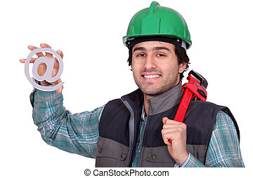 A handyman holding a at sign.