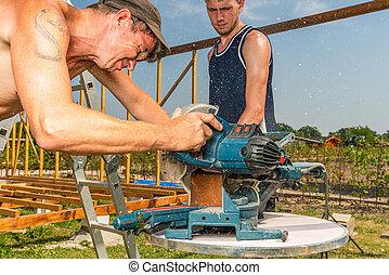handyman saws a wooden beam with a circular saw