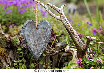 hanging wooden heart in front of a romantc garden - a ...
