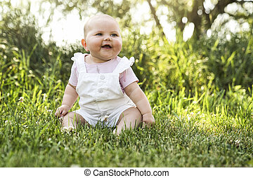Happy adorable chubby baby girl sitting on the grass