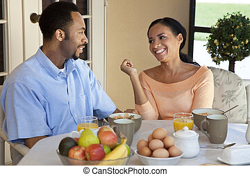 A happy African American man and woman couple in their thirties sitting outside having a healthy breakfast