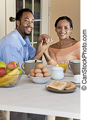 A happy African American man and woman couple in their thirties sitting outside having a healthy breakfast and holding hands.