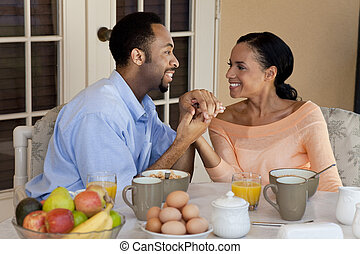 A happy African American man and woman couple in their thirties sitting outside holding hands and having a healthy breakfast