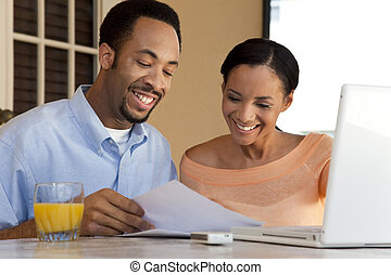A happy African American man and woman couple in their thirties working on a laptop computer and looking at paperwork