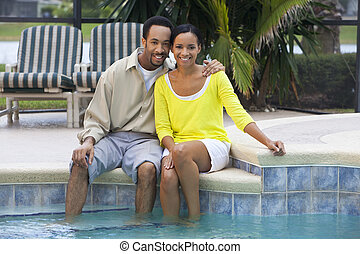 A happy African American man and woman couple in their thirties sitting with their feet in a swimming pool.