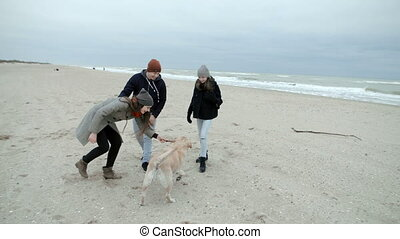A happy and harmonious young family is playing with a dog on the beach by the ocean.