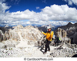 happy attractive woman mountain climber gives a thumbs up on a mountain peak in the Dolomites