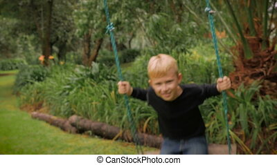 A happy blond boy having fun swinging on an old fashion tree swing - slowmo