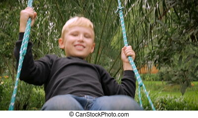 A happy blond boy swinging on a tree swing and smiling -...