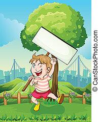 A happy boy near the tree with an empty board