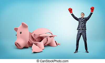A happy businessman has his hands raised up in victory while he stands beside a broken piggy bank.