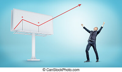 A happy businessman standing beside a large billboard with a red statistic arrow jumping out of it.