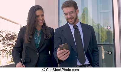 A happy businessman turning his smart phone horizontally on mobile app video