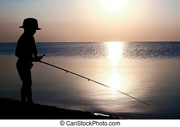 A Happy child fisherman fishing by the sea on nature ...