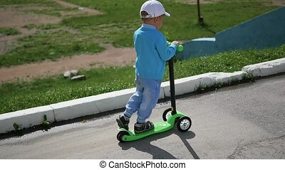 a happy child rides his scooter in the Park.Fun outdoors