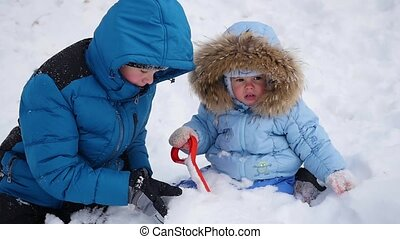a happy children plays with snow in the park. buried in the snow