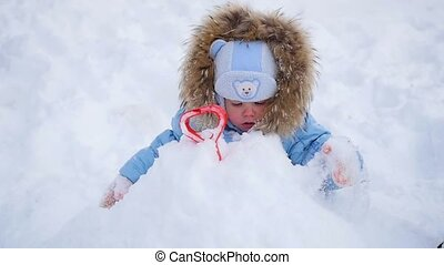 a happy children plays with snow in the park