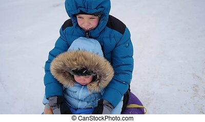 a happy children rides and smiling in snowtube on a snow