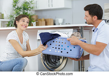 a happy couple doing laundry
