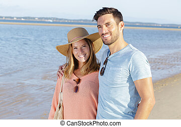 a happy couple enjoying the sea