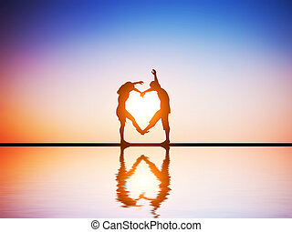 A happy couple in love making a heart shape with their bodies at sunset