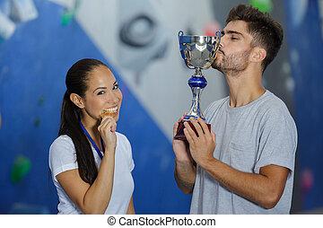 a happy couple kisses trophy