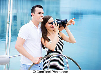 A happy couple on a boat looking through binoculars