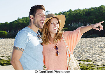 a happy couple pointing the beach